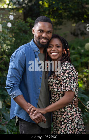 An African couple embracing each other in a garden - Stock Image