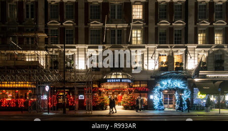 Exterior and entrance of the Rubens Hotel with Christmas decorations and lighting. Footman in doorway, pedestians walking on pavement. - Stock Image