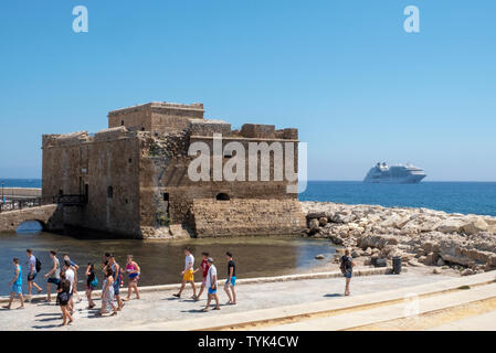 Paphos, Cyprus. A view of the Paphos Castle and the Seabourn Encore cruise liner anchored off the shore - Stock Image