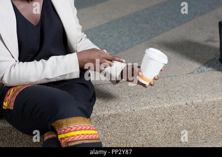 Young woman sitting at the terrace shows a bowl of coffee. - Stock Image