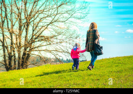 mom and daughter walk together outside . - Stock Image