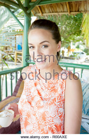 Young woman holding coffee cup - Stock Image