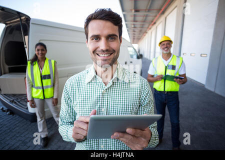 Portrait of manager using digital tablet and workers standing in background - Stock Image