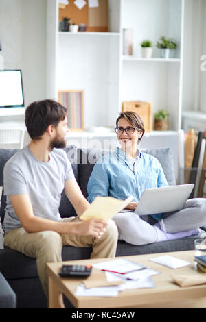 Young husband and wife consulting about family budget and discussing opportunity of travel - Stock Image