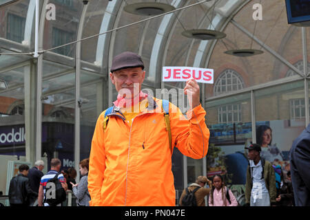 Elderly man wearing an orange anorak jacket holding up a JESUS sign standing at the entrance to Liverpool Street Station in London UK  KATHY DEWITT - Stock Image