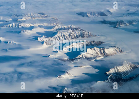 Greenland peaks cast long shadows over the snow. - Stock Image