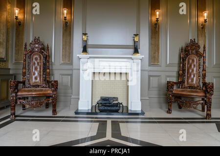 Fireplace and ornate wood and leather chairs in a stately home country house. - Stock Image