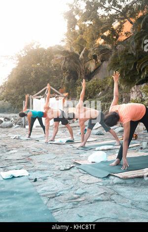 Group of multiple people exercising outdoors. Yoga retreat Puerto Vallarta - Mismaloya, Mexico - Stock Image