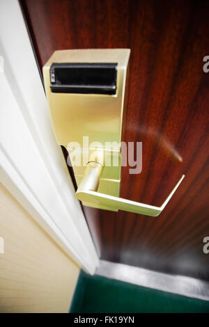 Hotel room brass electronic door lock and handle on a wooden door - Stock Image