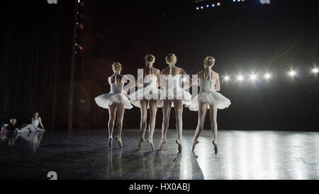 Low angle view of serious ballet dancers in costume performing onstage in show - Stock Image