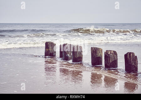 Wooden sea breakwater, selective focus, color toning applied. - Stock Image