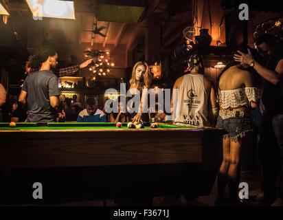 A transgender woman plays pool in a bar on Khao San Road, Bangkok. - Stock Image