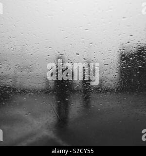 Two blurred figures standing in the rain, with rain drops on window - Stock Image