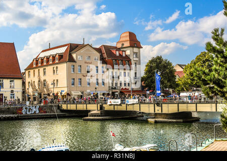 Tourists cross the bridge over the Alter Strom canal in the picturesque coastal town of Warnemunde, Germany. - Stock Image