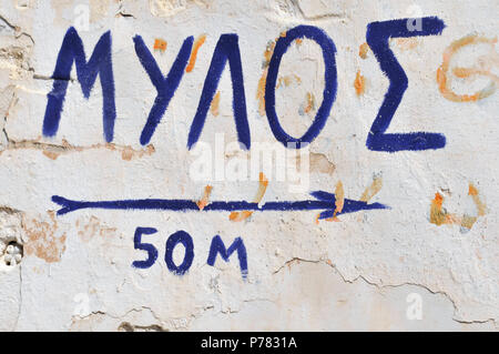 Greek sign painted on wall directing to a windmill - Stock Image