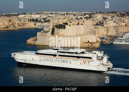The catamaran Jean de la Valette departing from Malta en route to Sicily, with Fort St Angelo in the background. Transport by sea in the EU. - Stock Image