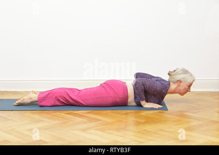 Senior woman with gray hair exercising yoga at home on a mat in front of a white wall, asana cobra, copy space - Stock Image