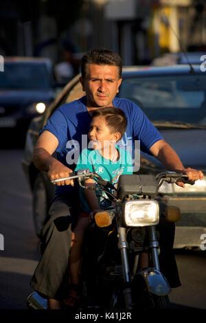 Iranian man and Son on a motorcycle, Shiraz, Iran - Stock Image