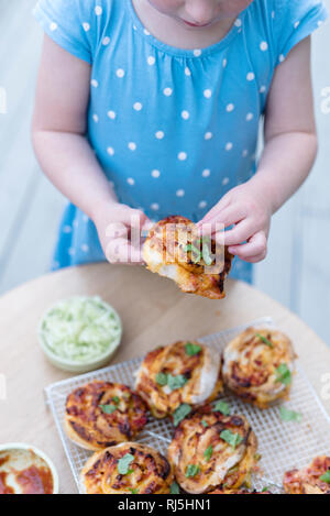 Girl decorating grilled buns with herbs - Stock Image