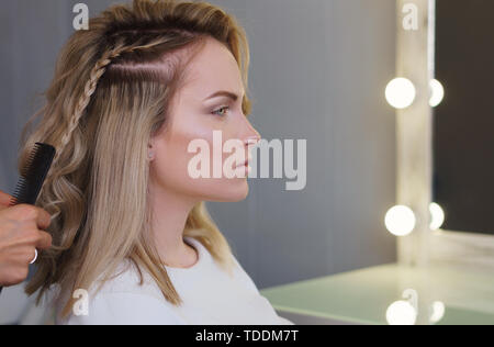 Hairdressing services. Creation of evening hairstyles fashionable stylish women's hairstyles. Hair styling process. Curls. Courses in hairdressing. Tr - Stock Image