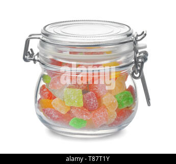 Glass jar full of colorful hard candies isolated on white - Stock Image