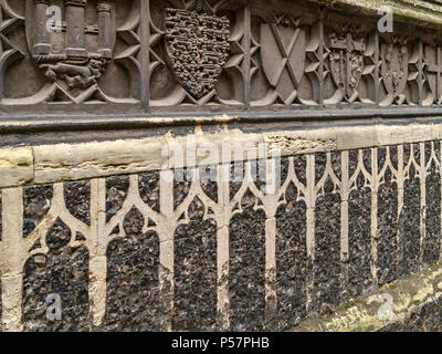 Old ornate carved stone and knapped flint masonry frieze along exterior wall of St. Andrews Church, Norwich, England, UK - Stock Image