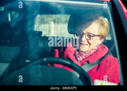 Happy old woman driving a car - Stock Image