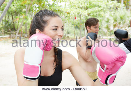 Young man and woman boxing on beach - Stock Image