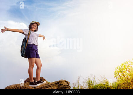 Happy hiker asian cute teens girl with backpack cap and glasses standing smiling poses open arms on mountain and - Stock Image
