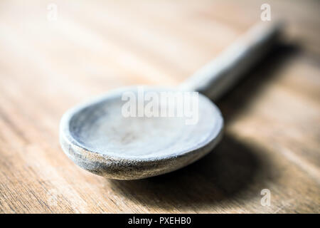 A Wooden Cooking Spoon Lying Down On A Table - Stock Image