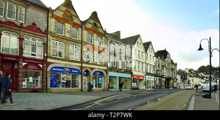 Looking down the main street, (Fore Street) in town of Okehampton with shops, South Devon, England, UK - Stock Image