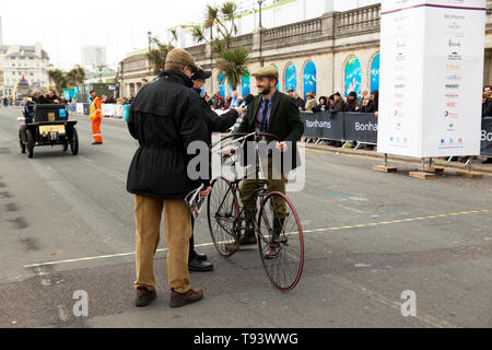 A Veteran Cyclist being interviewed, after successfully completing the  2018 London to Brighton Veteran Car Run course, as part of a successful trial. - Stock Image