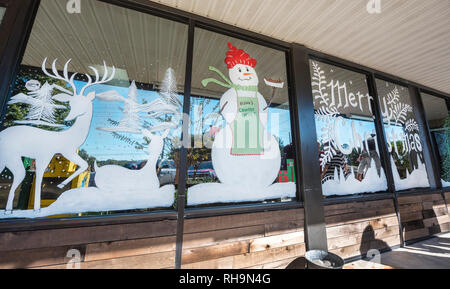 Christmas window decorations in a small town restaurant window, North Florida. - Stock Image