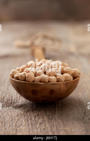 Chickpeas in a wooden spoon on the old wooden background close-up - Stock Image