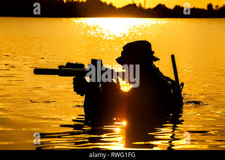 Silhouette of a special forces soldier with rifle, crossing a river in the jungle. - Stock Image