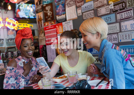 Young women friends using smart phone in bar - Stock Image