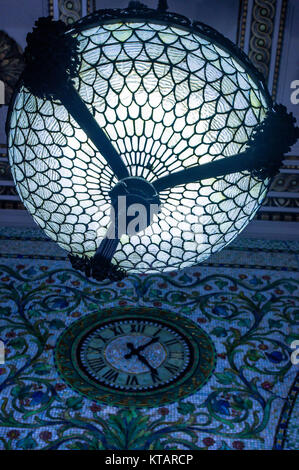 Glass light in chicago cultural centre with wall clock on ornately decorated wall. - Stock Image