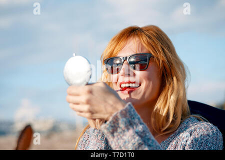 Attractive young woman refreshing her makeup lipstick by holding a handheld mirror powder box on a sunny day - Stock Image