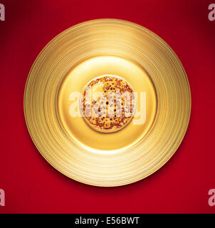 A crumpet on a golden plate - Stock Image