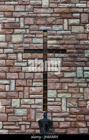 Christian cross on a wall of a church. - Stock Image