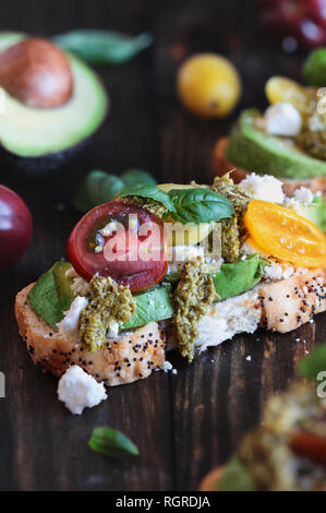 Avocado toast sandwich with avocados, pesto, fetaa cheese, fresh from the garden basil and heirloom tomatoes, over a rustic wooden background. Greek f - Stock Image