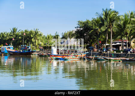 Traditional boats on Thu Bon River lined with Palm trees in old quarter of historic town. Hoi An, Quang Nam, Vietnam, Asia - Stock Image