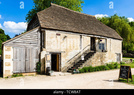 The granary is a shop located in a 2 storey barn with outside stone steps next to the Tythe Barn in Barton Farm country park - Stock Image
