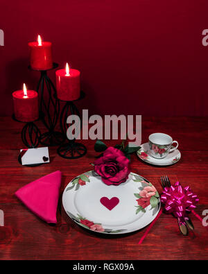 Floral pattern fine china dinnerware with matching plate, cup and saucer. pink rose, pink napkin, silverware, red candles and card - Stock Image