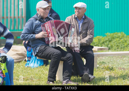 RUSSIA, Nikolskoe village, Republic of Tatarstan 25-05-2019: A group of old men sitting on the bench. One of them playing accordion. Mid shot - Stock Image