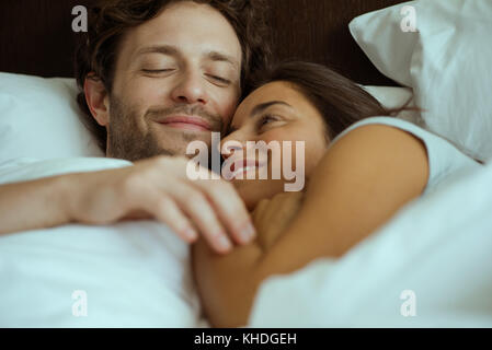 Couple embracing in bed - Stock Image