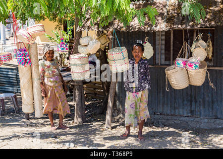 Dili, Timor-Leste - Aug 11, 2015: Two local elderly native East Timorese women, street vending traditional wicker baskets hanging on ropes, at a tin h - Stock Image