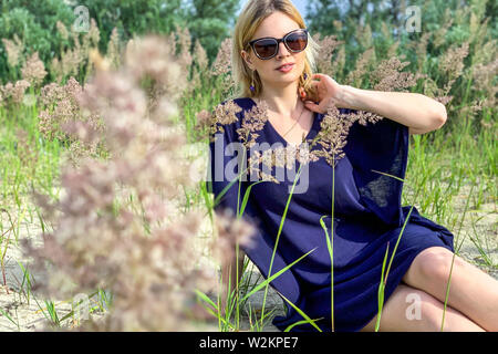 beautiful blonde woman in blue dress and sunglasses posing while sitting on ground among grass at summer meadow, posing and looking at camera. outdoor - Stock Image