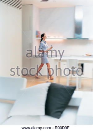 Blurred image of woman in modern kitchen - Stock Image