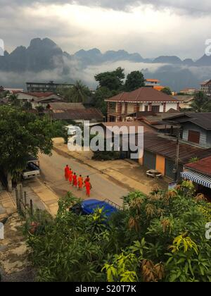 Monks walking to temple early morning in Vang Vieng Laos - Stock Image